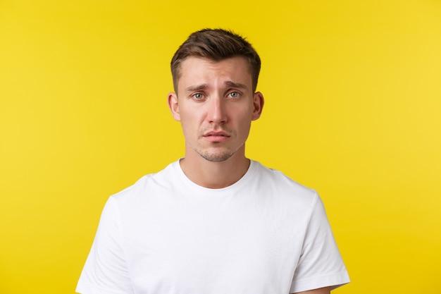 Concept d'émotions de mode de vie, d'été et de personnes. portrait en gros plan d'un jeune homme en détresse misérable à l'air sombre et triste, se sentant le cœur brisé ou fatigué, fronçant les sourcils sur fond jaune