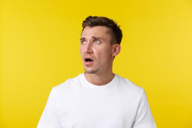 Concept d'émotions de mode de vie, d'été et de personnes. portrait en gros plan d'un jeune homme triste et fatigué déçu en t-shirt blanc, regardant dans le coin supérieur gauche, haletant et fronçant les sourcils contrarié par les mauvaises nouvelles.