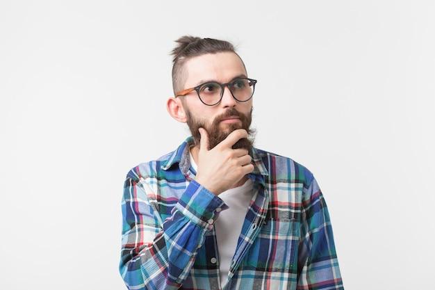 Concept d'émotions et de personnes - homme hipster barbu pensant à quelque chose sur fond blanc.