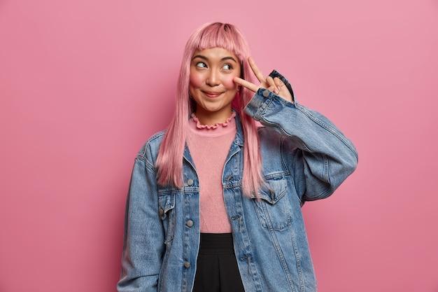 Concept d'émotions positives et d'attitude. sourire fille aux cheveux rose rêveuse donne signe vice-roi de la paix, montre deux doigts