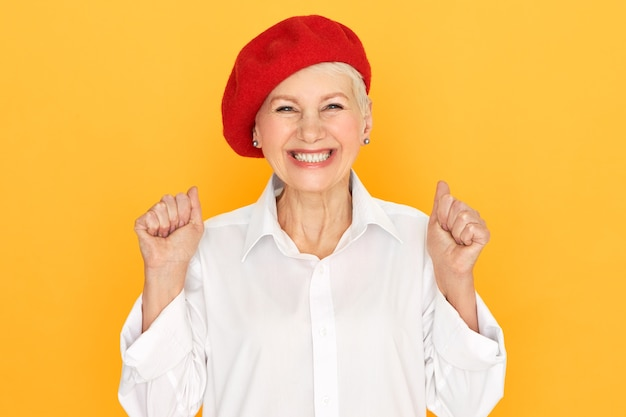 Concept d'émotions positives, de célébration, de joie et de bonheur. image de studio de femme mûre ravie extatique en élégant bonnet rouge s'exclamant avec enthousiasme, serrant les poings, célébrant les bonnes nouvelles ou le succès