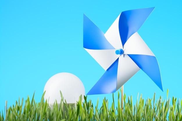 Le concept d'énergie «verte»: jouet moulin à vent et ampoule led sur l'herbe verte