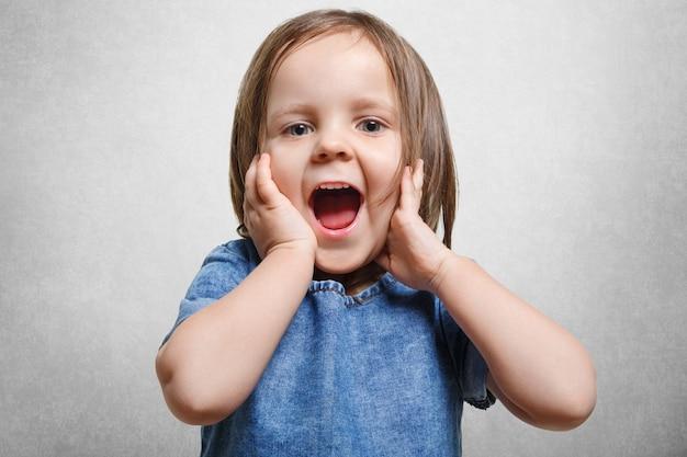 Concept d'enfance, de joie et de positivité heureux. fou de joie belle petite fille en robe denim à la mode, garde la bouche largement ouverte, heureuse de voir quelque chose d'agréable, isolé sur blanc.