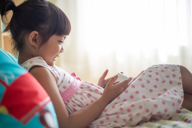 Concept enfant, technologie et internet - petite fille au lit avec smartphone à la maison