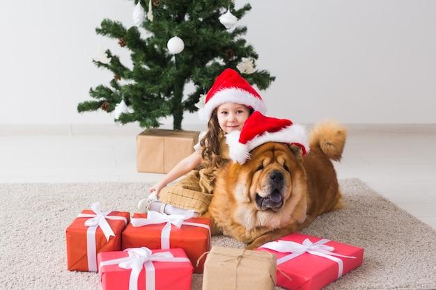 Concept d'enfants et d'animaux de compagnie - jolie fille avec un chien chow assis près de l'arbre de noël. joyeux noël et bonnes vacances.