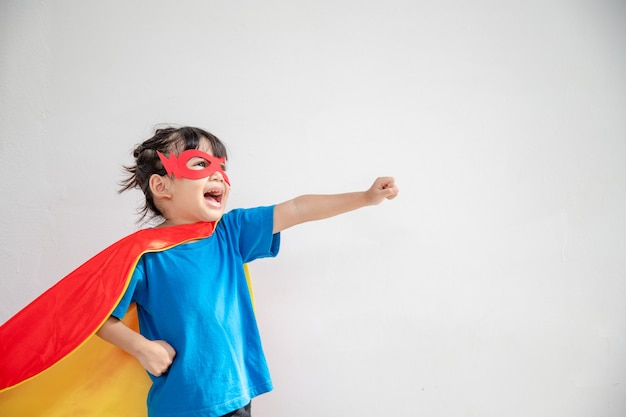 Concept d'enfants, fille souriante jouant au super héros sur fond blanc