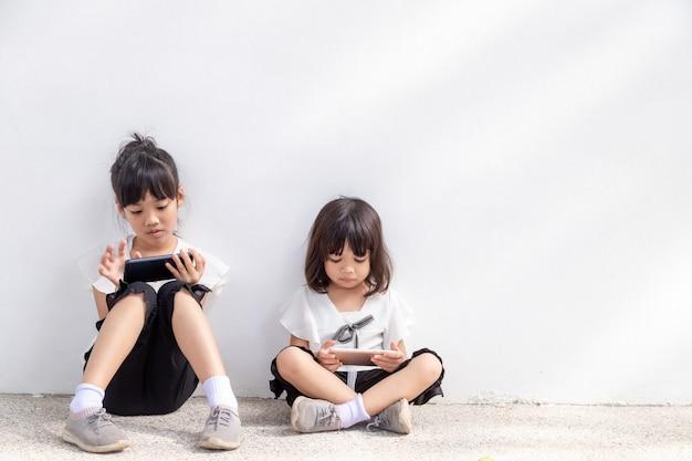 Concept enfants et gadgets deux petites filles sœurs frères et sœurs regardent le téléphone