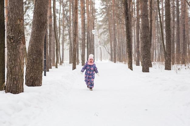 Concept d'enfants et de la nature - adorable petite fille marchant dans le parc d'hiver