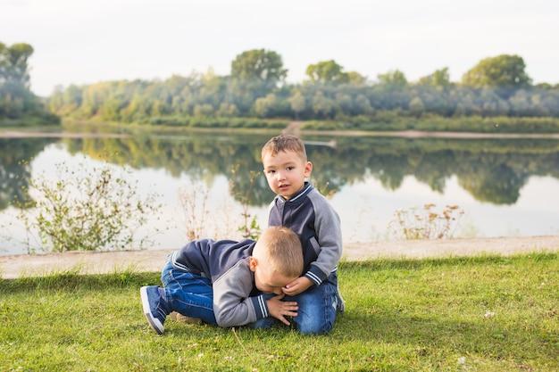 Concept d'enfants et de la nature. deux frères assis sur l'herbe sur fond de nature