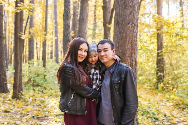 Concept d'enfants, de nature et de famille - portrait de famille heureuse sur fond de parc d'automne.