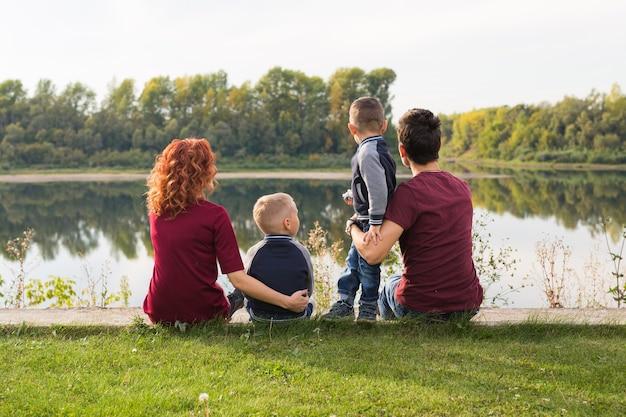 Concept d'enfants, de parentalité et de nature - grande famille assise sur l'herbe
