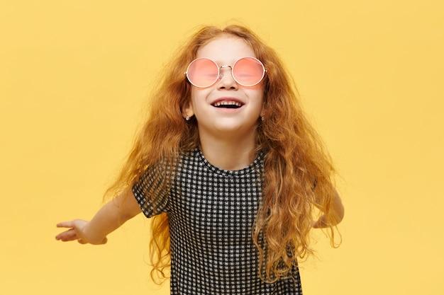 Concept d'enfants, de style et de fshion. petite fille à la mode insouciante aux cheveux roux bouclés ayant une expression faciale joyeuse heureuse, riant, portant des lunettes de soleil roses élégantes, gardant les bras derrière son dos