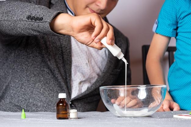 Concept d'enseignement et de formation en chimie. gros plan sur un garçon et son père faisant une expérience chimique à domicile, faisant de la boue à partir de colle, de tétraborate de sodium et de colorants