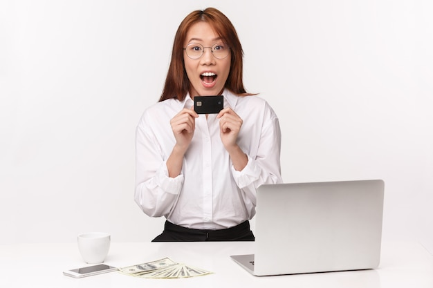 Concept d'entrepreneurs de carrière, de travail et de femmes. close-up portrait cheerful young asian woman sitting in office with laptop, money, hold credit card, look amusé, got first paycheck
