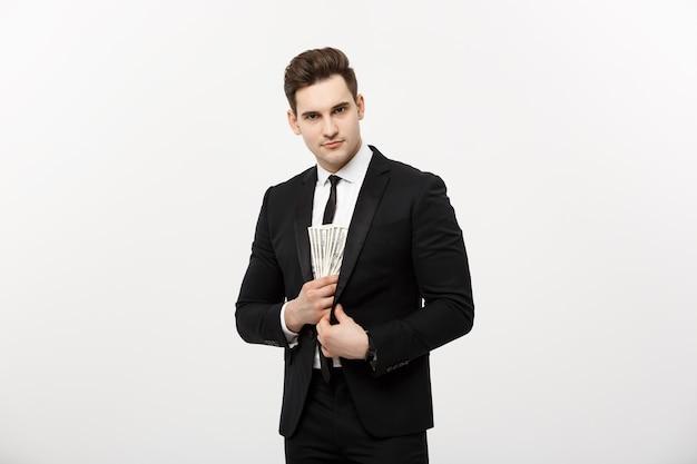 Concept d'entreprise : bel homme d'affaires en costume noir prenant des billets en dollars avec une expression furtive sur fond blanc.