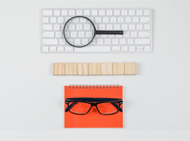 Concept d'entreprise avec des blocs de bois, des lunettes, une loupe sur le clavier sur un fond blanc à plat.