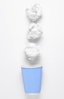 Concept d'entreprise de bureau. boules de papier, tasse de café vide sur fond blanc.
