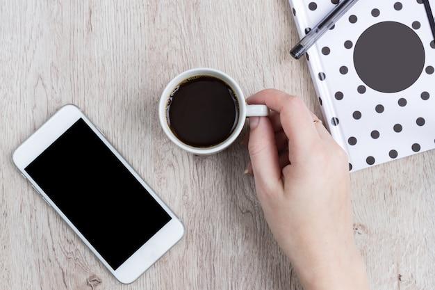 Concept d'entreprise et de bureau - cahier à couverture noir et blanc à pois, smartphone et tasse de café noir sur une table en bois. vue de dessus.