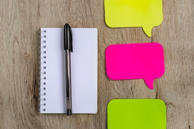 Concept d'entreprise et de bureau - cahier vierge, des autocollants et un stylo noir sur une table en bois. lay plat minimal, vue de dessus.