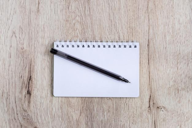 Concept d'entreprise et de bureau - cahier vierge un stylo noir sur une table en bois. lay plat minimal, vue de dessus.