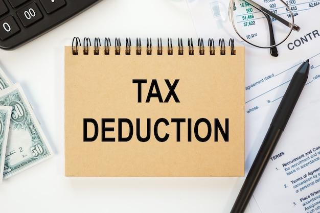 Concept d'entreprise - bureau de l'espace de travail et ordinateur portable écrit la déduction fiscale