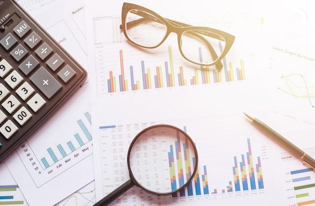 Concept d'entreprise avec crayon lunettes calculatrice et loupe sur les documents. graphiques et graphiques d'entreprise