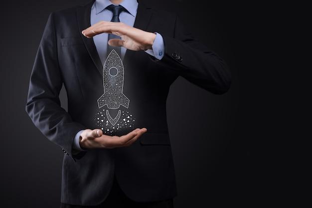 Concept d'entreprise de démarrage, homme d'affaires détenant une fusée transparente d'icône se lance et s'envole de l'écran avec une connexion réseau sur un mur sombre.
