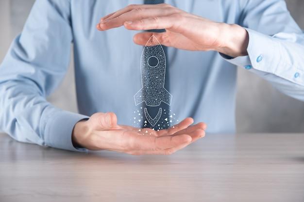 Concept d'entreprise de démarrage, homme d'affaires tenant une fusée transparente d'icône se lance et s'envole de l'écran avec une connexion réseau sur une surface sombre