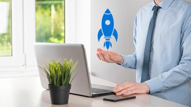 Concept d'entreprise de démarrage, homme d'affaires tenant une tablette et une fusée d'icônes se lance et monte en flèche depuis l'écran avec une connexion réseau sur fond sombre