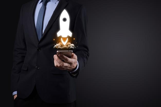 Concept d'entreprise de démarrage, homme d'affaires tenant la tablette et l'icône de la fusée est en cours de lancement