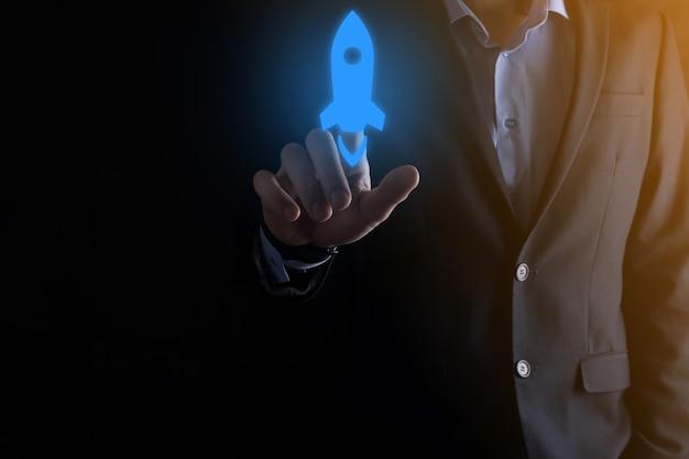 Concept d'entreprise de démarrage, homme d'affaires tenant la tablette et l'icône fusée se lance et s'envole de l'écran avec une connexion réseau sur fond sombre.