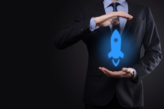 Concept d'entreprise de démarrage, homme d'affaires tenant la tablette et l'icône de la fusée se lance et s'envole de l'écran