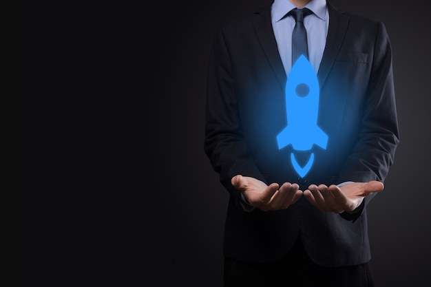 Concept d'entreprise de démarrage, homme d'affaires tenant la tablette et l'icône de la fusée se lance et s'envole en flèche
