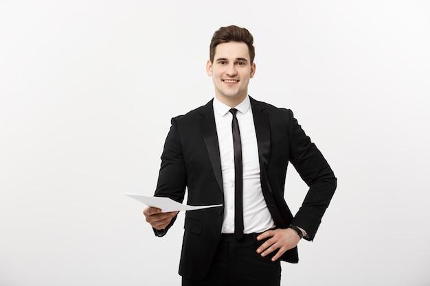 Concept d'entreprise et d'emploi : homme élégant en costume tenant un curriculum vitae pour l'embauche dans l'intérieur blanc brillant.