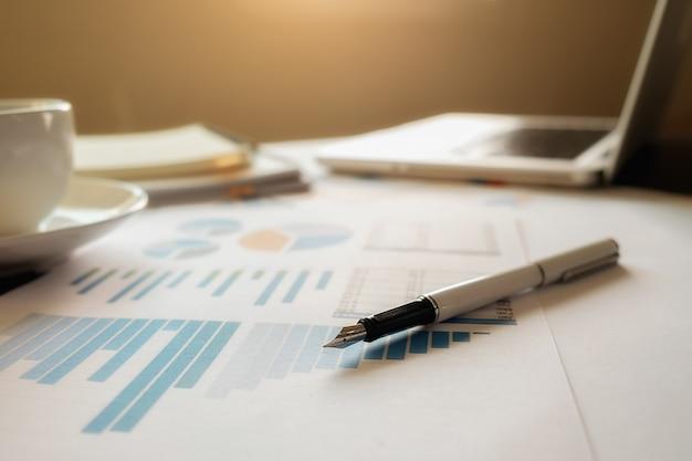 Concept d'entreprise avec espace de copie. table de bureau avec stylo et tableau d'analyse, ordinateur, ordinateur portable, tasse de café sur le bureau. tonalité de rétro filtre rétro, mise au point sélective.