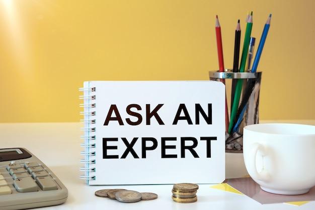 Concept d'entreprise - espace de travail bureau et ordinateur portable écrit demandez à un expert