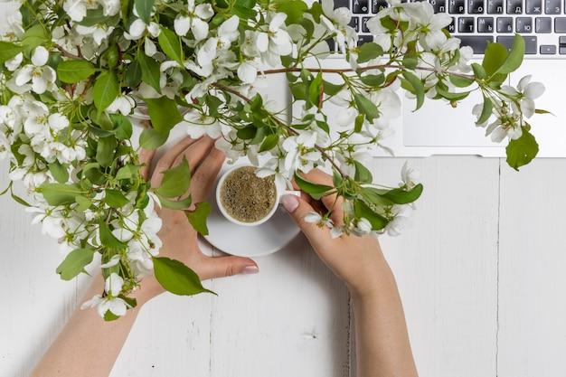 Concept d'entreprise féminine avec ordinateur portable, bouquet de fleurs de printemps et mains de femme tenant une tasse de thé ou de café chaud