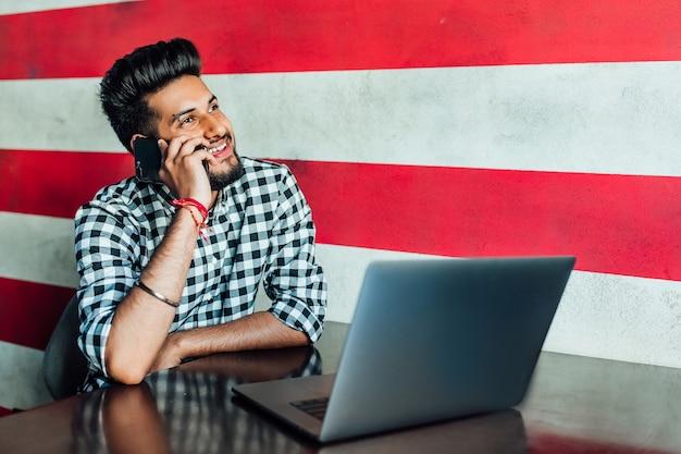 Concept d'entreprise. gai jeune homme africain en tenue de soirée utilisant son ordinateur portable tout en se penchant au bar.