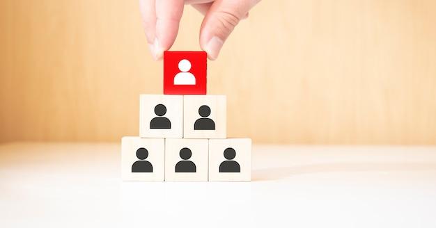 Concept d'entreprise de gestion des ressources humaines et de recrutement, main mettant le bloc de cube de bois sur la pyramide supérieure, espace de copie