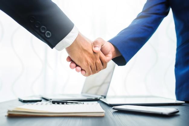 Concept d'entreprise, handshake d'homme d'affaires dans l'espace de travail de bureau pour l'investissement