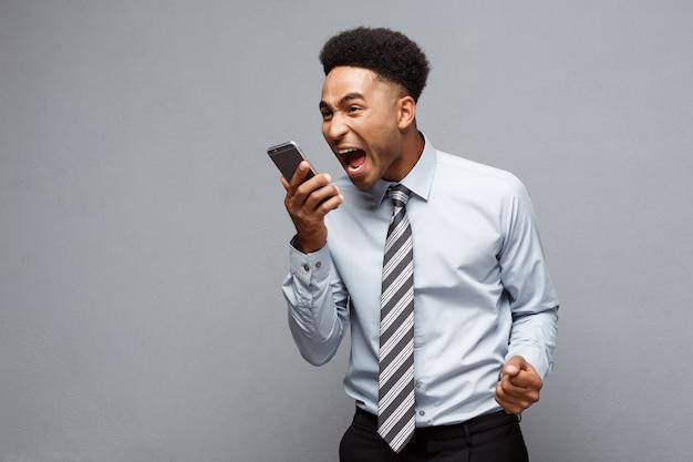 Concept d'entreprise - homme d'affaires afro-américain stressant criant et criant sur téléphone mobile.
