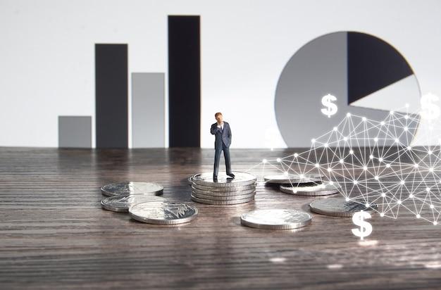 Concept d'entreprise. homme d'affaires debout sur un tas de pièces d'argent.