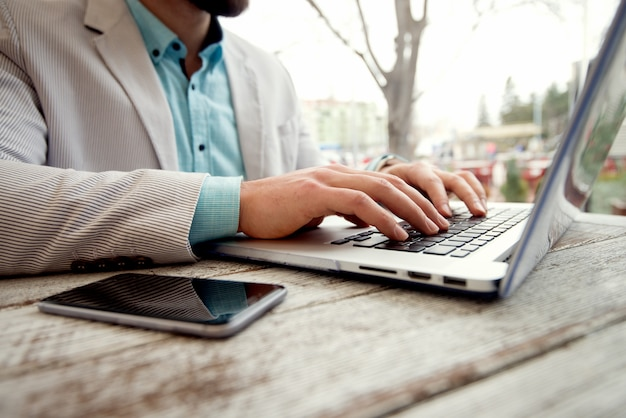 Concept d'entreprise. homme tapant clavier d'ordinateur portable faible profondeur de champ.