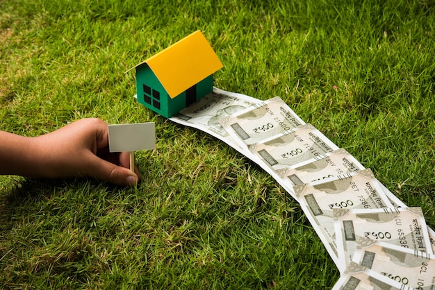 Concept d'entreprise immobilière indienne montrant une maison modèle 3d avec des clés, des billets en papier et une calculatrice. mise au point sélective