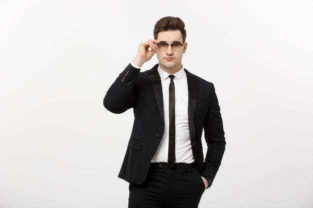 Concept d'entreprise : jeune bel homme d'affaires portant des lunettes tenant la main dans la poche isolé sur fond blanc.