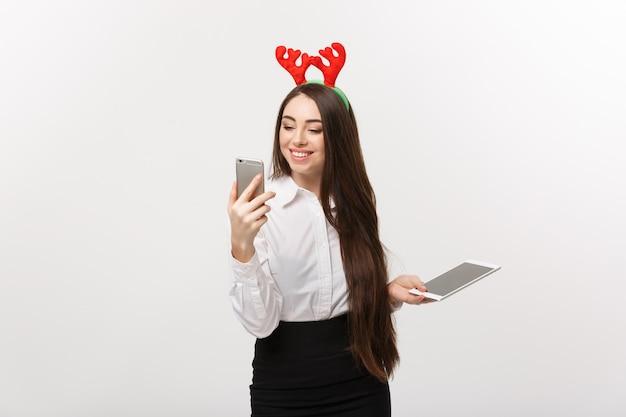 Concept d'entreprise - jeune femme d'affaires caucasienne dans le thème de noël jouant au téléphone moblie avec une expression faciale surprenante.