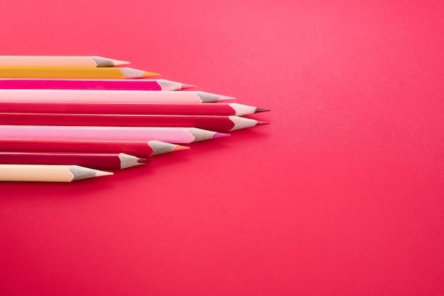 Concept d'entreprise de leadership. crayon de couleur rouge mène autre couleur sur fond rose