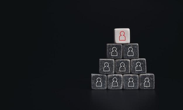 Concept d'entreprise de leadership, de gestion des ressources humaines et de recrutement. symbole d'icône humaine rouge sur des blocs de dés blancs avec des pièces noires, forme pyramidale sur fond sombre avec espace de copie, style minimal.
