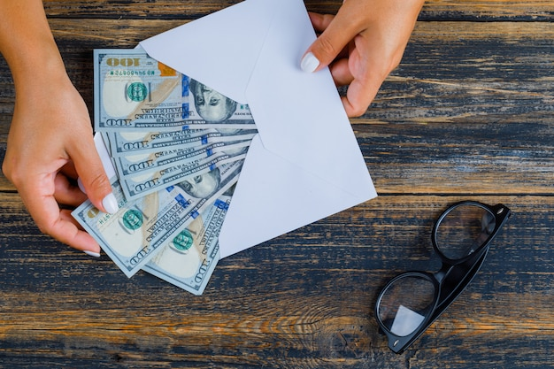 Concept d'entreprise avec des lunettes et une enveloppe avec de l'argent sur une surface en bois