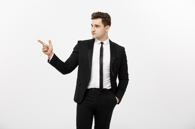 Concept d'entreprise : portrait en gros plan d'un jeune homme ou d'un homme d'affaires de courtier boursier brunete à succès pointant sur un fond avec son doigt sur fond blanc.